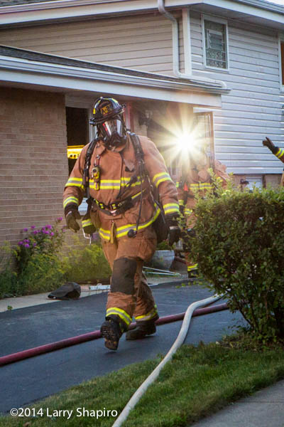 fireman walking at a fire scene with full PPE