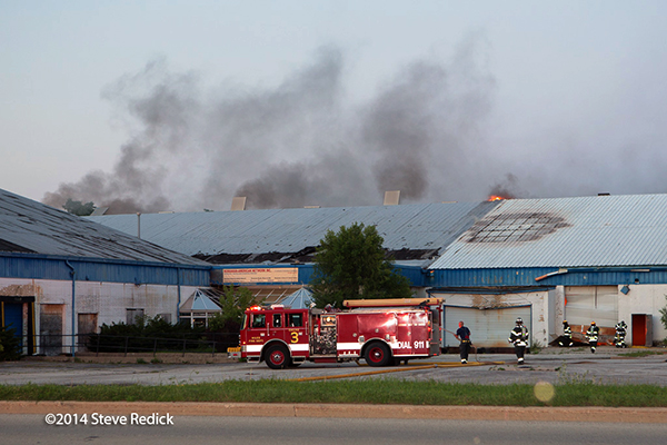 fire engine by warehouse with lots of smoke