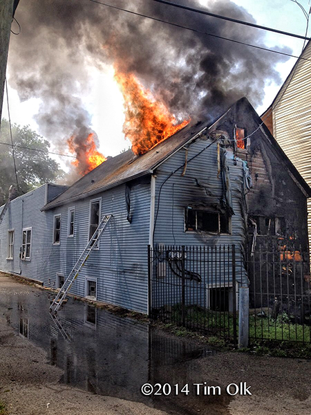 flames burn through the roof of a house