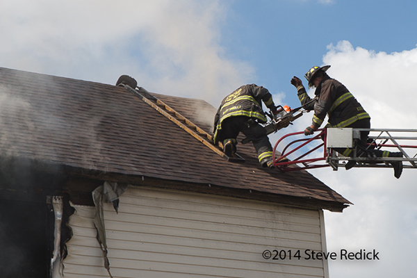 firemen ventilate roof of house