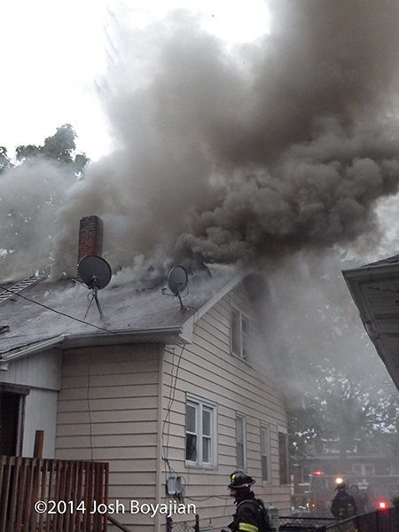 heavy smoke from roof of house fire