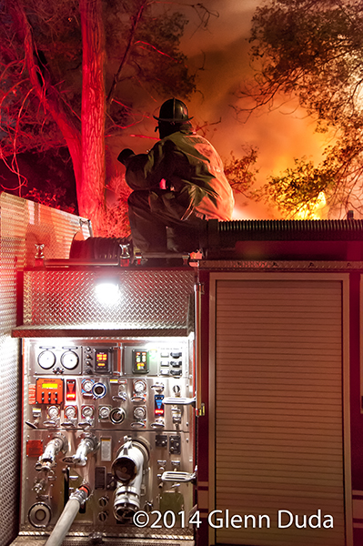 fireman operating deck gun at night