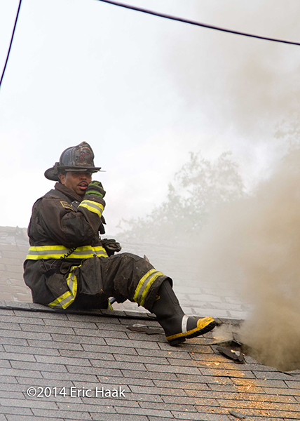 firemen with axes venting peaked house roof during fire
