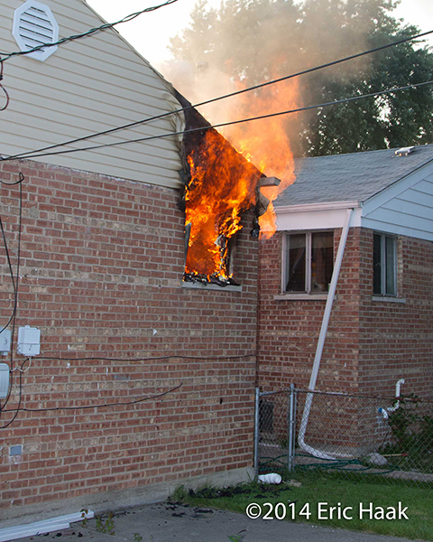 flames shoot out the window of a house