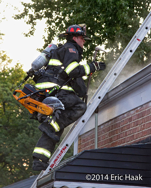 firefighter climbing ladder with saw and other tools