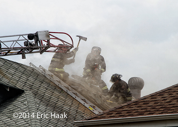 Chicago firemen venting the roof of a house