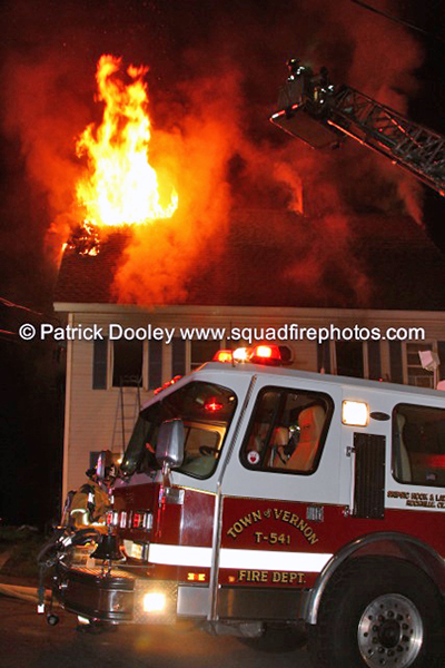big flames through the roof of house fire at night