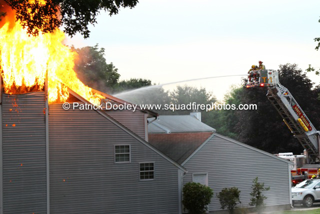 flames trough the roof of a townhouse