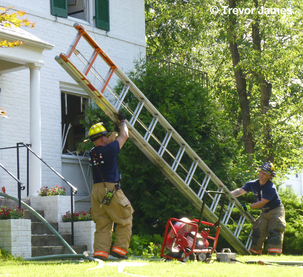 fireman picking up tools after a fire