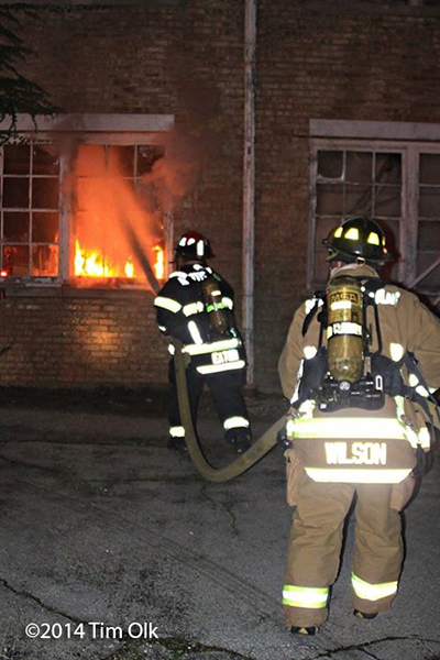 firemen with hose line attacking a fire