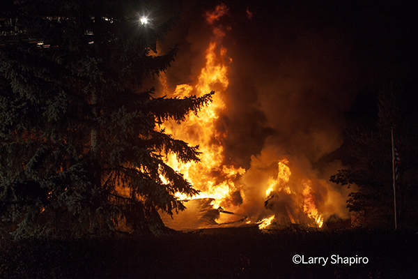 big flames through the roof of a building at night