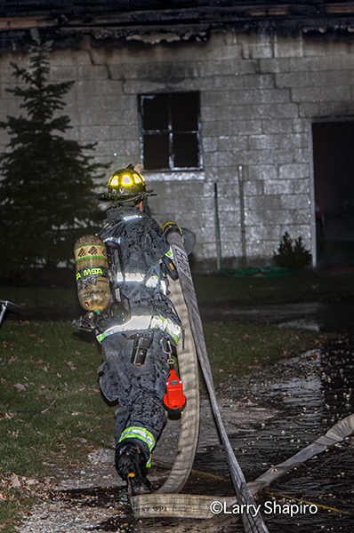 fireman pulling hose at night