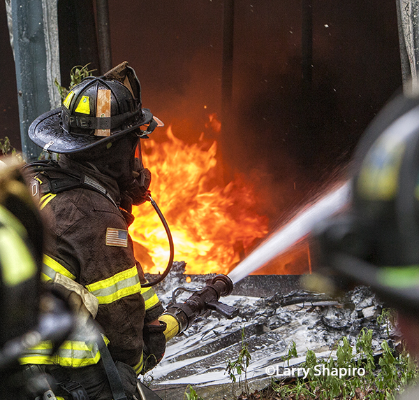 fireman with hose fights flames