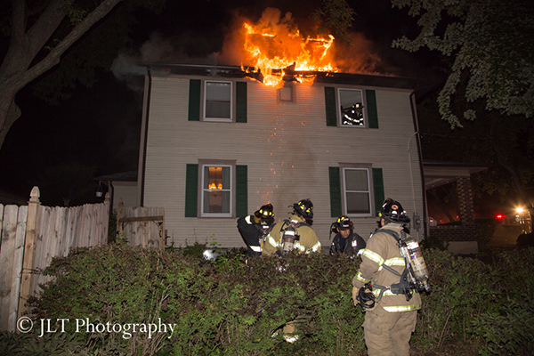fire through the roof of a house at night