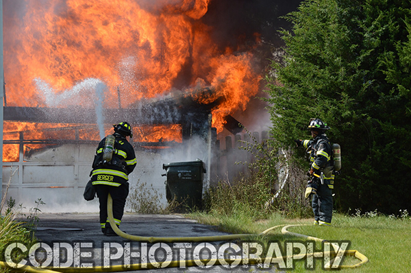 fireman approaches fully involved garage fire