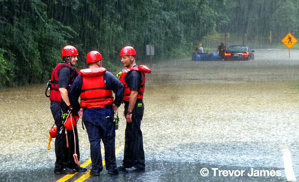 firemen rescue a woman trapped during a storm