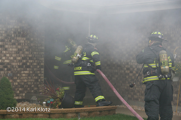 Firemen making entry with hose into house fire