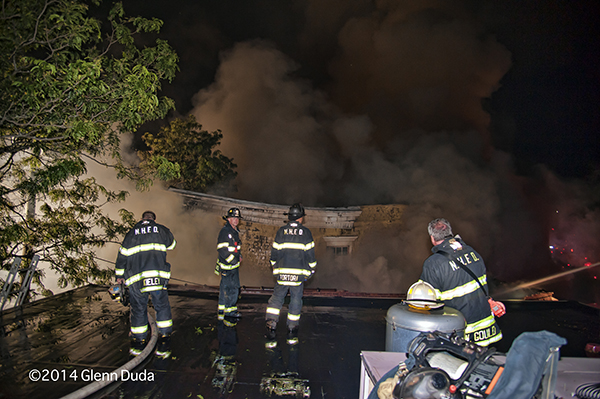 firemen on roof at night fire scene