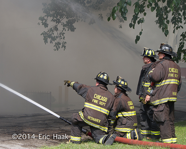 firefighters with hose at smokey fire scene