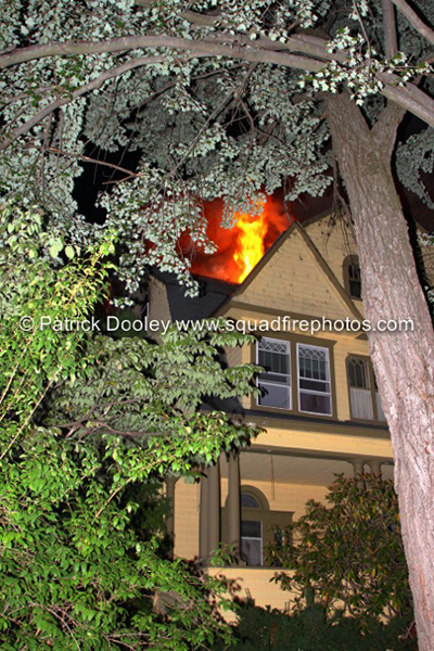 fire through the roof of house at night