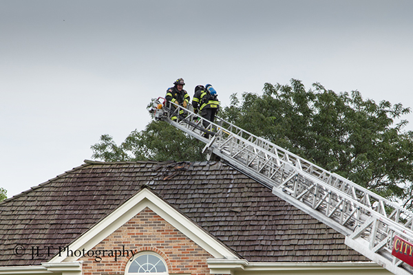 firemen on the tip of an aerial ladder