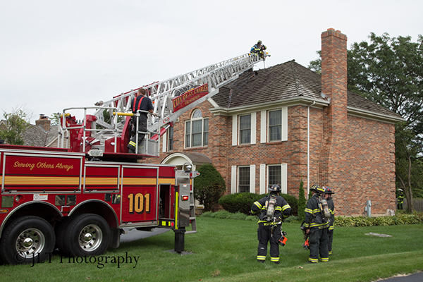 fire truck ladder to the roof of a house