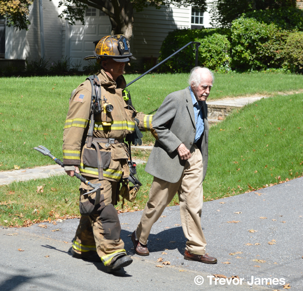 firefighter escorts elderly man