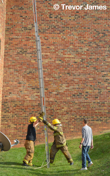 firemen with ladder at fire scene