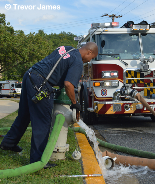 firemen with hose at hydrant