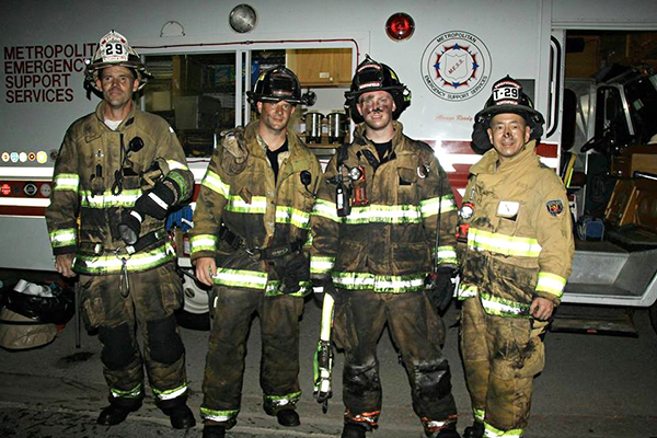 firemen in filthy gear after junkyard fire