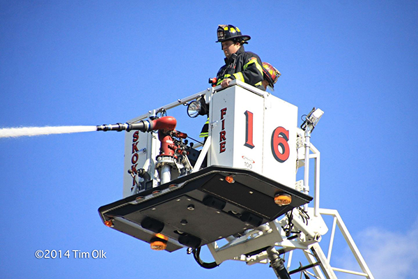 firemen deploy master stream in Pierce tower ladder