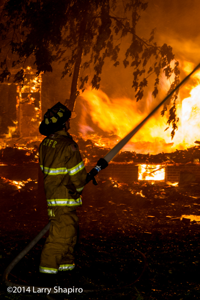fireman with hose line and burning house