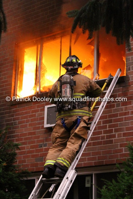 fire blows out a window with fireman working on a ladder