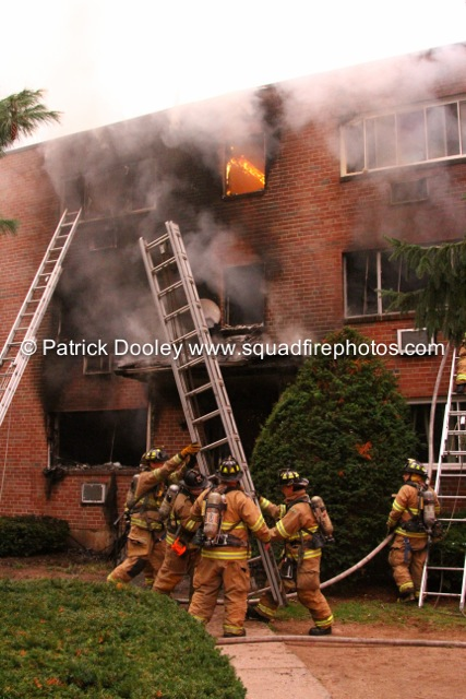 fire blows out a window with firemen moving a ground ladder