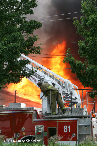 massive flames with fireman and ladder truck