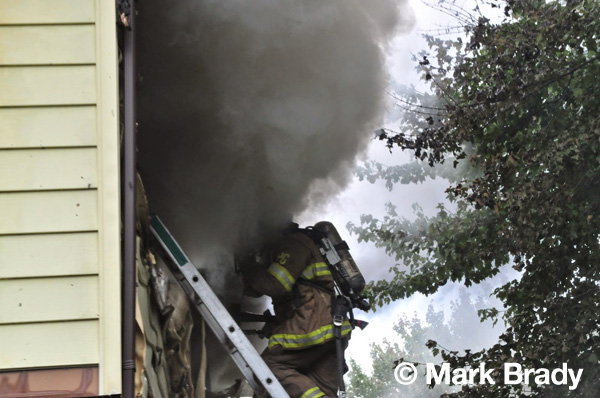 firemen on ladder at window of house fire