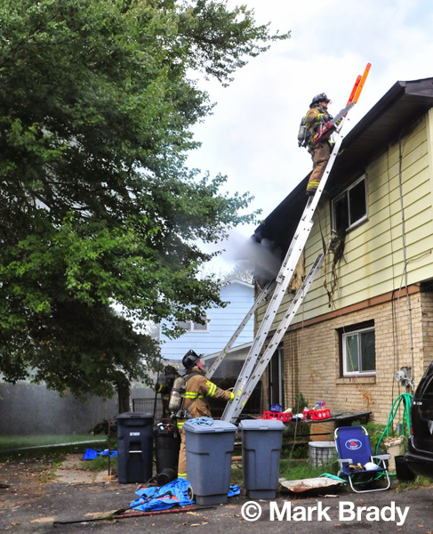 fireman on a ladder to the roof of a house fire