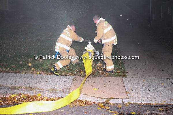 two firemen open hydrant at night