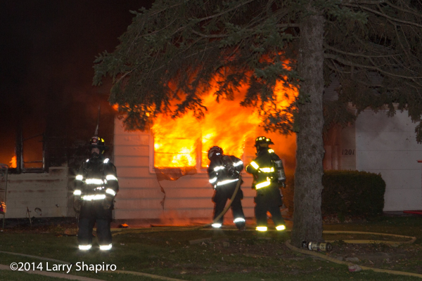 firemen with house full engulfed in flames