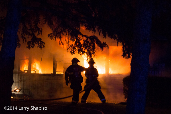 silhouette of firefighters at house fire