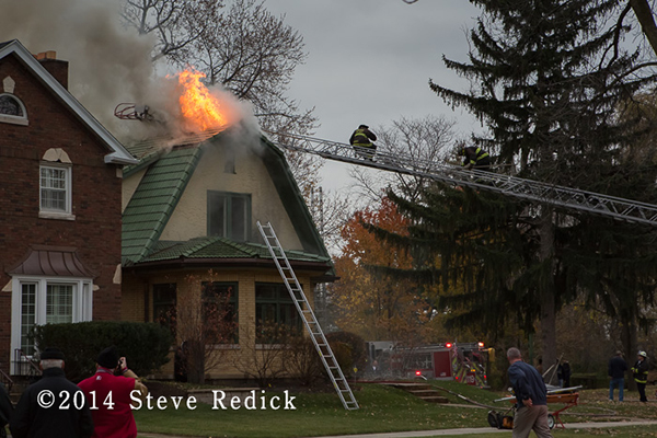 firemen on a ladder with fire through the roof of a house