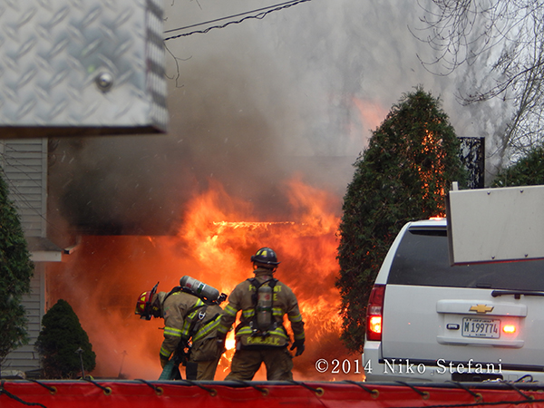 firemen at house fire with big flames