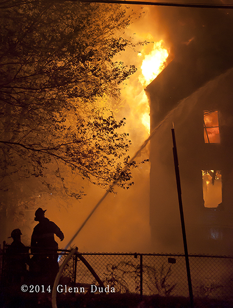 silhouette of firemen at night fire scene