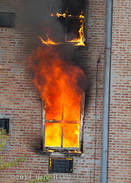 fire blows out of apartment window
