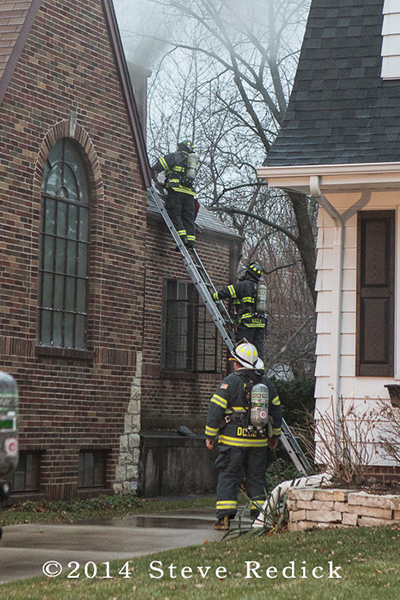firemen on ladder at house fire