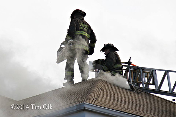 firemen with saw on roof at house fire