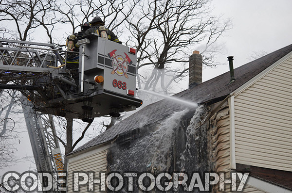 firemen in tower ladder bucket at fire scene