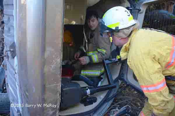 firefighters extricate victims from car