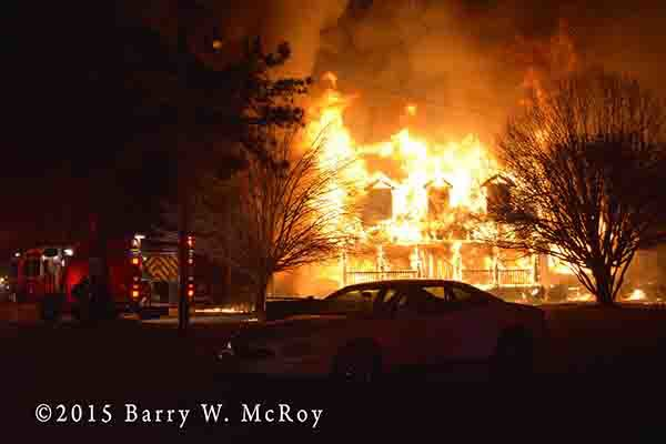 huge house fully engulfed in flames at night