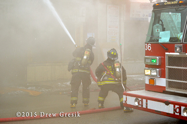 firemen with hose in smoke
